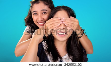 Two smiling Asian female friends play guess who game. One girl covering her friend's eyes from behind, over blue background - stock photo