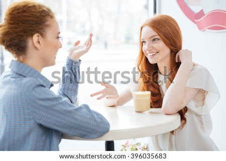 Two smiling attractive young women drinking coffee in cafe together - stock photo