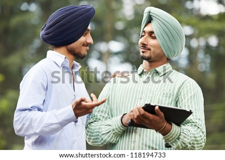 Two smiling authentic native indian punjabi sikh men in turban discussing something with tablet computer - stock photo