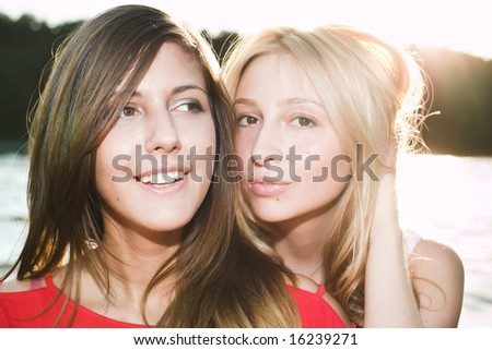Two smiling beautiful girls in red - stock photo