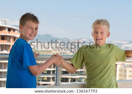 Two smiling boys in colored T-shirts are shake hands on the background of building under construction, focus on right boy. - stock photo