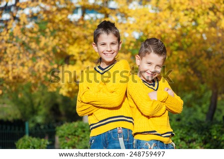 Two smiling brothers in the park on an autumn day standing back to back with crossed arms and looking at camera. - stock photo