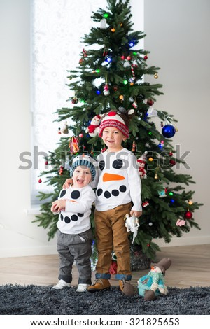 Two smiling brothers standing near christmass tree - stock photo
