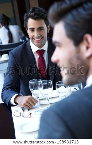 Two smiling business men have dinner at restaurant - stock photo