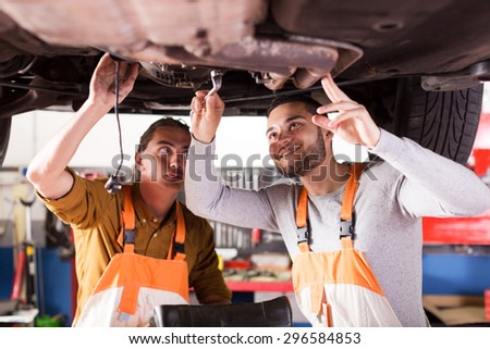 two smiling car mechanics at workshop at work. Focus to the right man - stock photo