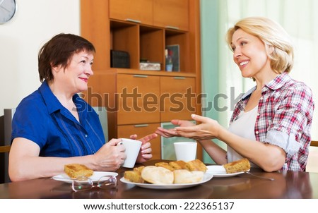 Two smiling colleagues in years drinking tea and chatting during pause for lunch - stock photo