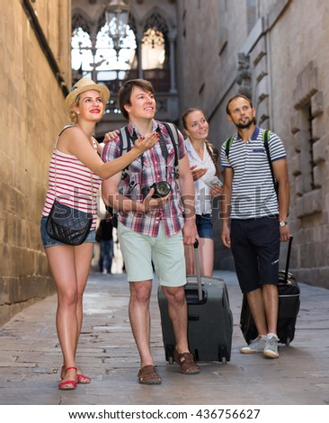 Two smiling couples with travel bags walking through the city. Selective focus - stock photo