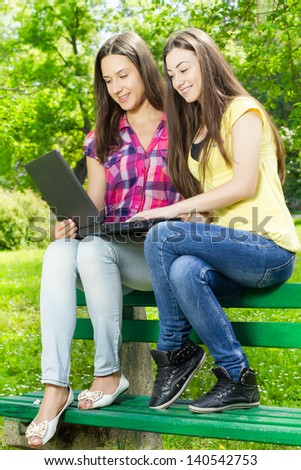 Two smiling female students using laptop in nature. - stock photo