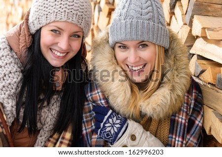 Two smiling friends in winter jackets countryside wooden logs background - stock photo