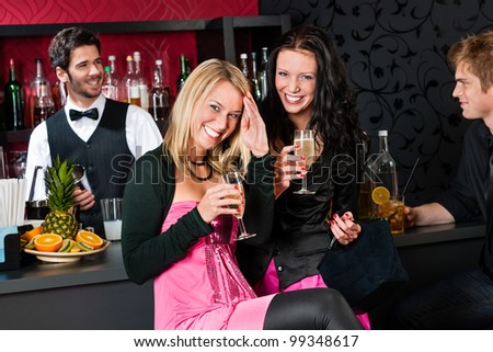 Two smiling girl friends enjoy glass of champagne at bar - stock photo