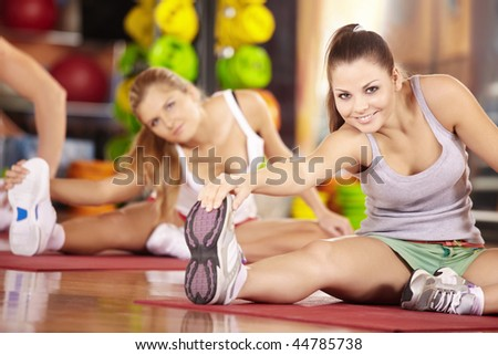 Two smiling girls do exercise in sports club - stock photo