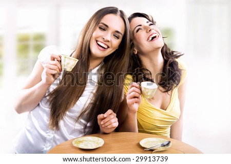 Two smiling girls have coffee time - stock photo