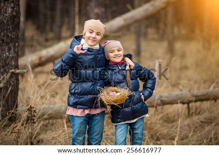 Two smiling girls posing with basket full of Easter eggs at forest - stock photo