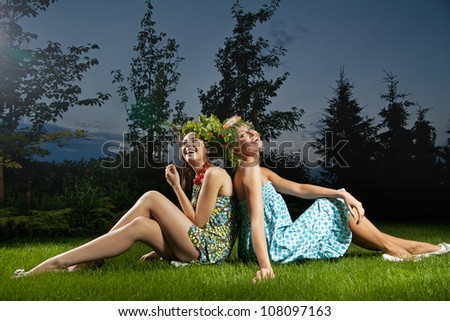 Two smiling girls sitting in a beautiful garden - stock photo