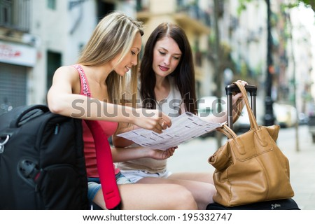 Two smiling girls with luggage sitting and reading the map at street - stock photo