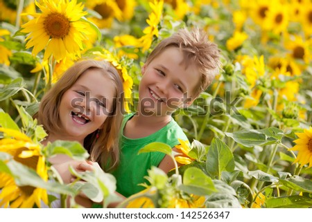 Two smiling happy children in sunflowers field - stock photo