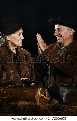 Two smiling hunter in western clothes closeup - stock photo