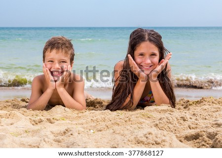 Two smiling kids on the beach lying down together near coastline - stock photo