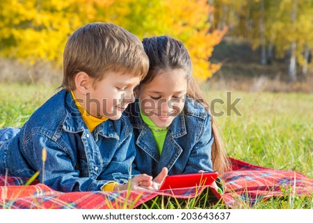 Two smiling kids playing with tablet pc on the autumn park - stock photo
