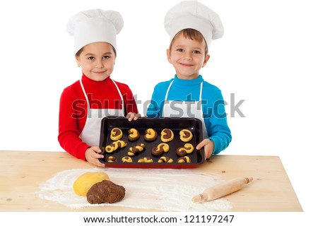 Two smiling kids with baking on oven-tray, isolated on white - stock photo