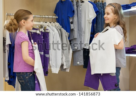 Two smiling little girls trying on the same dress in the store childrens clothes, focus on right girl - stock photo