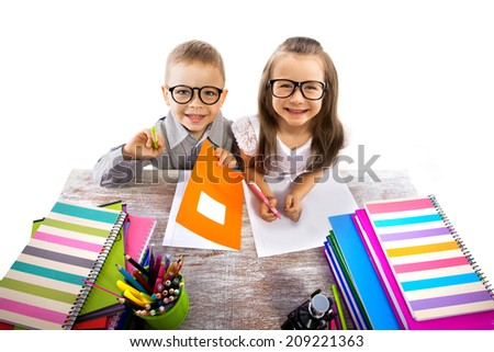 Two smiling little kids at the table children doing homework, isolated on white background. School, education concept. - stock photo