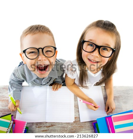 Two smiling little kids at the table in classroom at lesson. School, education concept. - stock photo