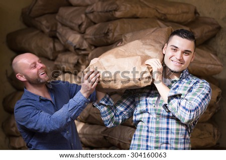 Two smiling loaders handling sacks with something heavy indoors - stock photo