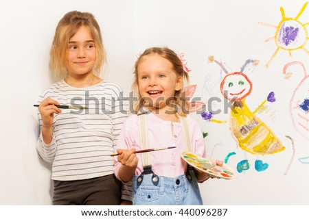 Two smiling painters drawing funny picture - stock photo