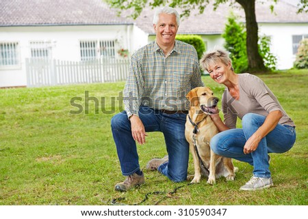 Two smiling senior people sitting with dog in front of their house in the garden - stock photo