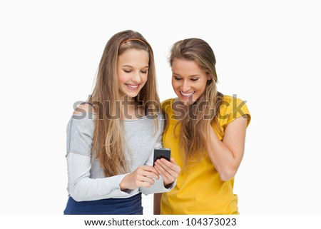 Two smiling students looking a cellphone screen against white background - stock photo