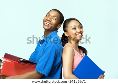 Two smiling students standing back to back carrying books. Horizontally framed photograph - stock photo
