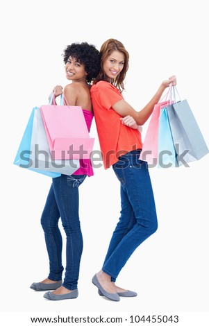 Two smiling teenage girls proudly holding shopping bags - stock photo