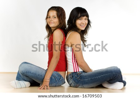 Two smiling teenage girls sitting back-to-back on the floor, caucasian/white. - stock photo