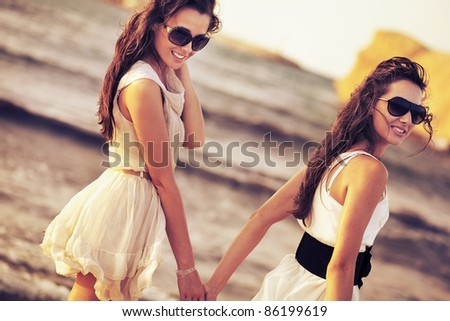 Two smiling woman on the beach - stock photo