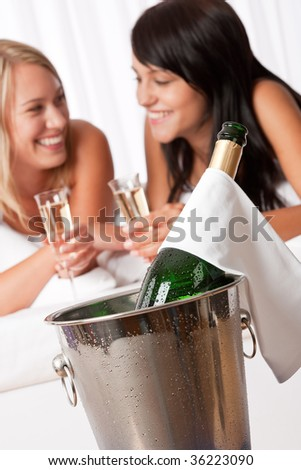Two smiling women drinking champagne in luxury hotel room, focus on bottle - stock photo