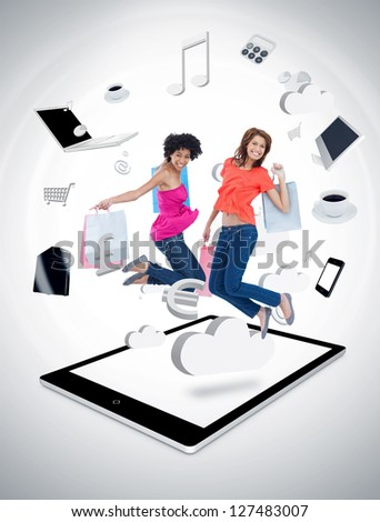 Two smiling women jumping on a tablet pc against a digital gray background - stock photo