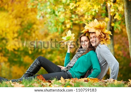 Two Smiling young attractive people with autumn maple leaves in park at fall outdoors date - stock photo