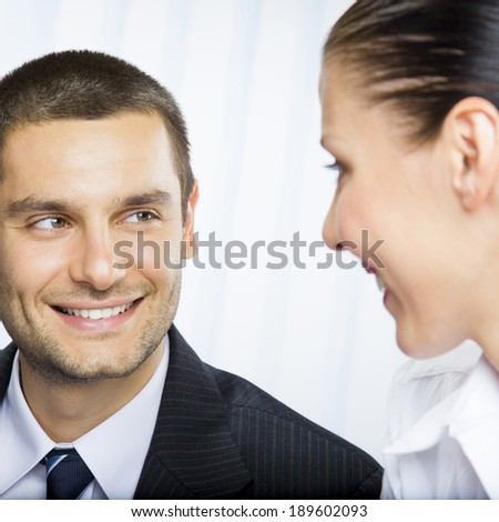 Two smiling young businesspeople or businessman and client, working at office - stock photo