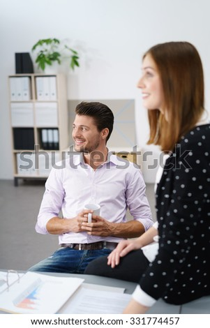 two smiling young businesspeople talking while having a coffee break - stock photo