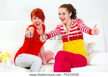 Two smiling young girlfriends sitting on sofa and showing thumbs up gesture - stock photo