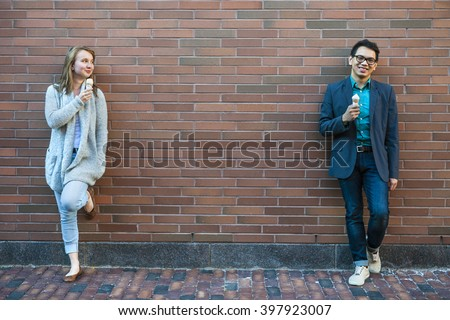 Two smiling young people holding ice cream cones standing apart near brick wall with copy space - stock photo