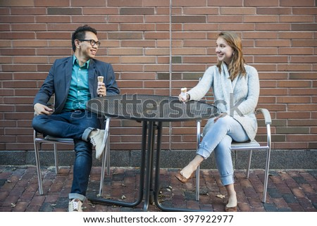 Two smiling young people with ice cream sitting at outdoor cafe table near brick wall having conversation - stock photo