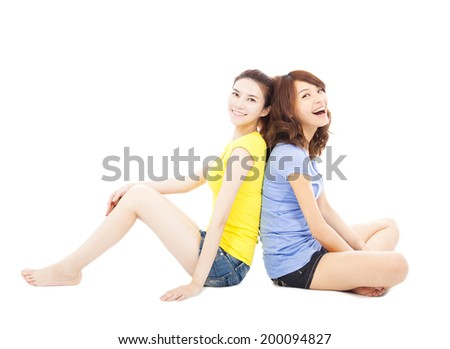 two smiling  young woman sitting and back to back - stock photo