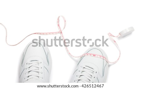Two sneakers and meter over white background. Loss weight concept image - stock photo