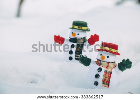 two Snow man stand among pile of snow in park. Sunshine is warming but cold at Hokkaido, Japan. - stock photo