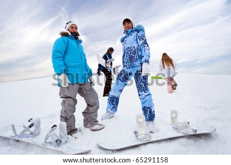 Two snowboard rider girls stay on hill and two fritnds walk up - stock photo