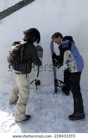 Two snowboarder putting snowboards down - stock photo