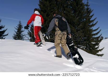 two snowboarder walking in the snow - stock photo