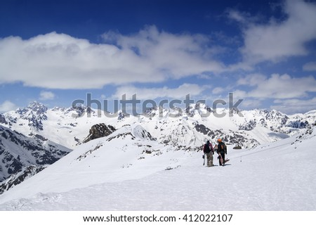 Two snowboarders on the ski resort at sun day. Caucasus, region Dombay. - stock photo